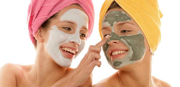 Chicas aplicándose arcilla en la cara